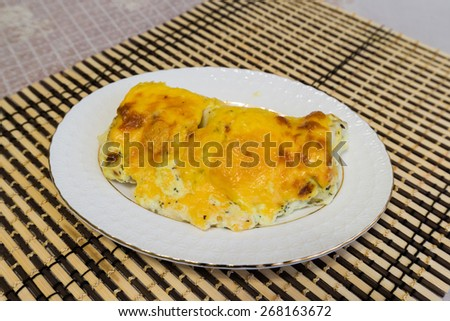Cod fillets with cheese sauce on a plate - stock photo