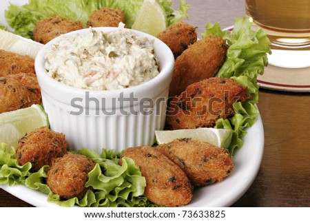 "Cod fish cakes (croquettes) with chunky tartar sauce. Typical dish made up of potatoes, codfish, eggs and parsley. Also known as ""Bolinhos de bacalhau"" in Brazil or ""Pasteis de bacalhau"" in Portugal. - stock photo"