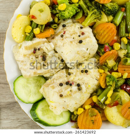 Cod fish on plate with vegetables - stock photo