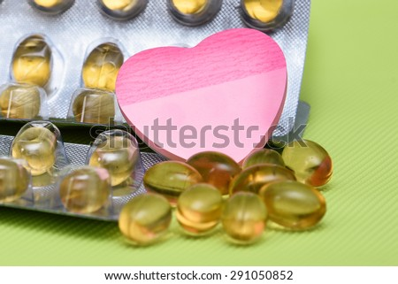Cod liver fish oil omega 3 gel capsules isolated on green background. heart shaped paper copy space for text. metal foil blister strip packaging.nutritional supplement  contains Vitamin A, Vitamin D - stock photo