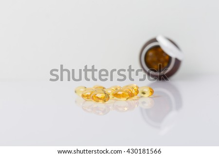 Cod liver oil capsules with a brown bottle on white with copy space - stock photo