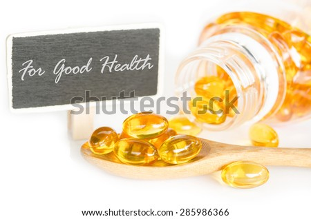 Cod liver oil omega 3 gel capsules and For good health tag on white background. - stock photo