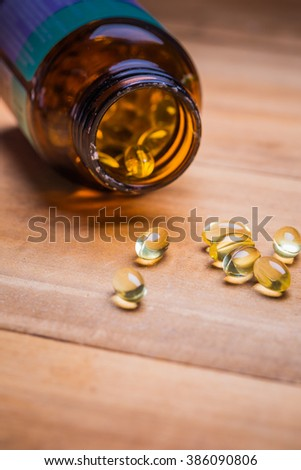 Cod liver oil omega 3 gel capsules isolated on wooden background. Vitamin D pills. dietary supplement