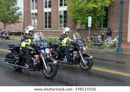 COEUR D ALENE, IDAHO 6/14/2014: Car d' Alene 2014 a city wide car show; Unidentified police officers riding motorcycles start of the parade of vintage cars.  - stock photo
