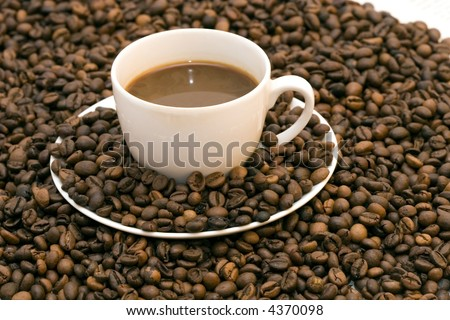 Coffe beans in cup on coffee background