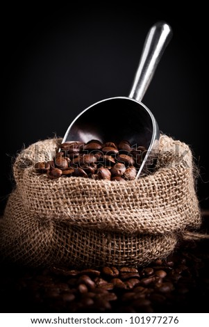 Coffe beans spilling from burlap bag - stock photo