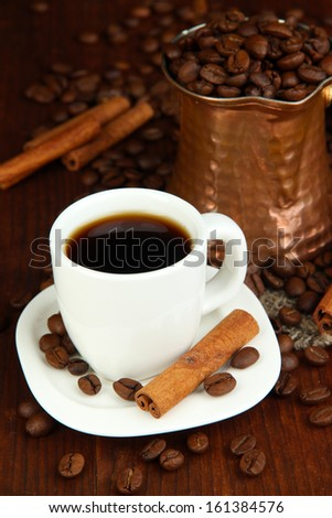 Coffe cup and metal turk on wooden table - stock photo