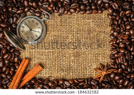 Coffe frame made of beans on burlap with star anise, cinnamon and retro watch - stock photo