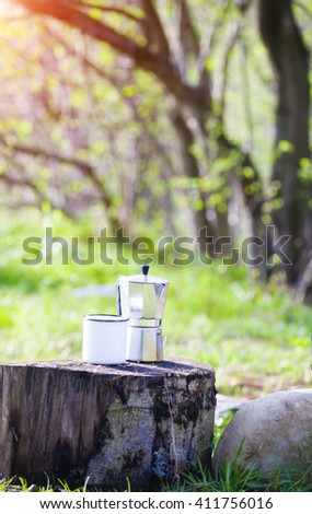 Coffee and a mug for a cheerful morning are camping outdoors - stock photo