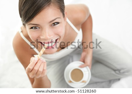 Coffee and cookie woman. Beautiful Asian / Caucasian woman enjoying coffee with a cookie. - stock photo