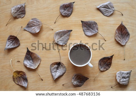 Coffee and dried leaves on wooden background