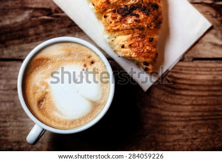 Coffee and fresh croissant for breakfast on rustic wooden table, top view. Chocolate croissant with cappuccino - stock photo