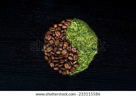 Coffee and Green Tea in a Yin Yang shape against a black wooden background - stock photo