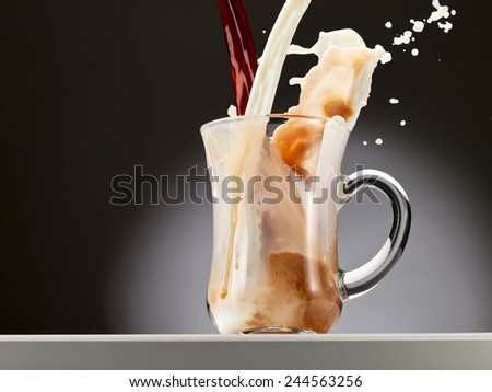 Coffee and milk pour and up from a glass - stock photo
