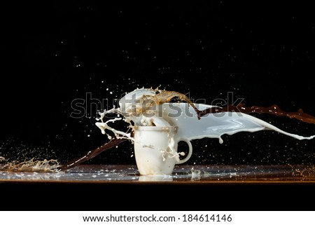 Coffee and milk pouring in a cup with splashes and drops, on black background - stock photo