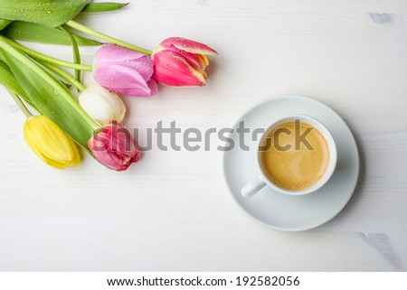 Coffee and tulips on a white wood table with some water on the tulips - stock photo