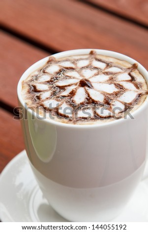 coffee art in a white cup on wooden background