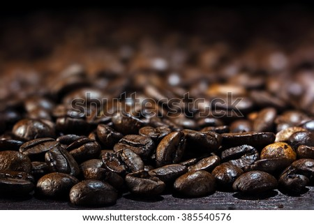 coffee background, closeup of dark brown roasted beans, copy space in the blurred background, selected focus, very narrow depth of field - stock photo