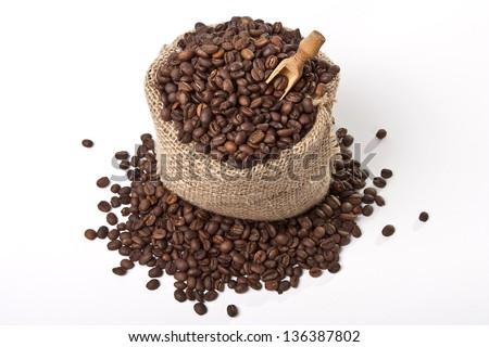 Coffee bag with scoop and spilled coffee beans - stock photo