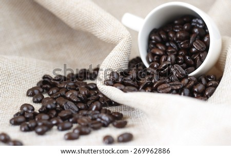 coffee bean flowing from white coffee cup on bleached jute cloth (selective focus) - stock photo