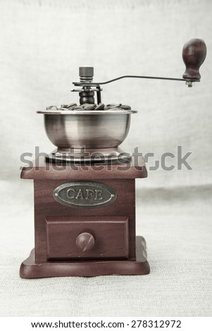 Coffee bean grinder is on the burlap sack background.