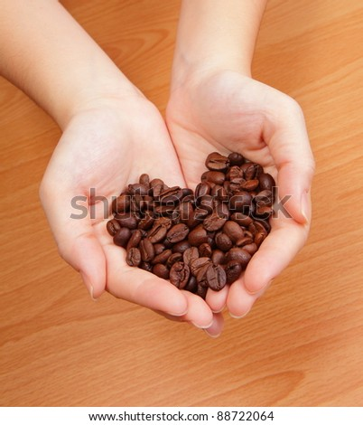Coffee bean in the hand and coffee bean is love heart shape - stock photo