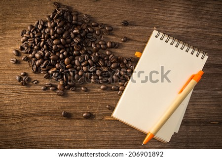 Coffee bean with notepad and pen - stock photo