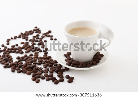Coffee beans and a cup of coffee on the table - stock photo