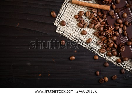 Coffee beans and chocolate on rustic dark wooden table - stock photo