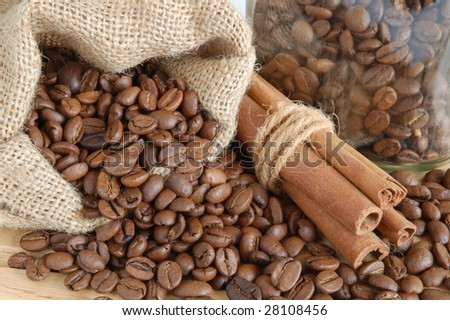 Coffee beans and cinnamon sticks in canvas sack on wooden background - stock photo
