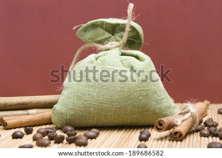 Coffee beans and cinnamon sticks in canvas sack on wooden background. Green bag - stock photo