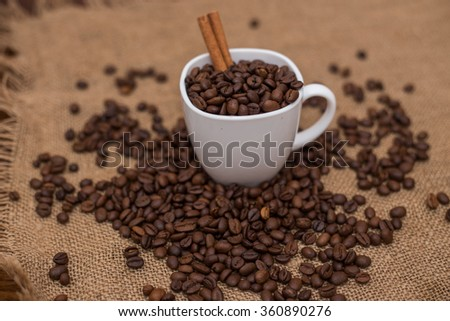 coffee beans and cinnamon white cup and saucer on a table brown texture units large lot of grain