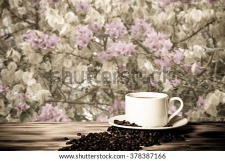 Coffee beans and coffee in white cup on wooden table opposite a defocused blossom background. Collage. Selective Focus. - stock photo