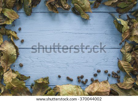 Coffee beans and coffee leaf on a white table top are made of wood at the edges - stock photo
