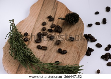 coffee beans and cone and christmass tree branch on wooden surface