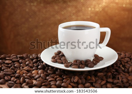 Coffee beans and cup of coffee on table on brown background - stock photo