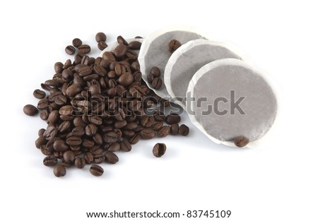 Coffee beans and pads on a white background.