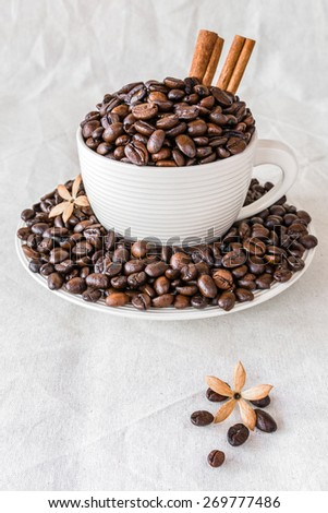 Coffee beans and white cup with cinnamon on canvas background