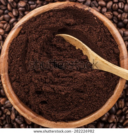 coffee beans and wooden bowl full of ground coffee on the table background - stock photo