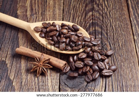 Coffee beans and wooden spoon on wooden board  - stock photo
