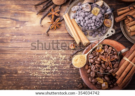 Coffee beans, chocolate drops, vanilla pods, cinnamon sticks, anise stars and brown sugar in a vintage silver cups on a dark textural wooden background. selective Focus - stock photo