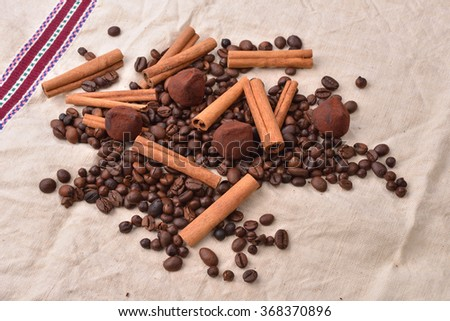 Coffee beans, cinnamon sticks and truffles on vintage texture, jute background. Morning pleasures. Awakening flavors. Selective focus - stock photo