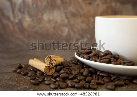 Coffee beans, cinnamon sticks, and white coffee cup, over stone background. - stock photo