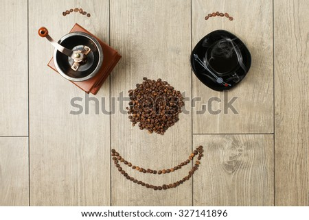 coffee beans,coffee cup and old coffee mill on wood deck looks like smile   - stock photo