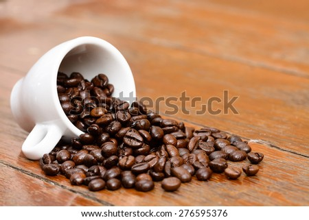 Coffee beans cup on old wooden table