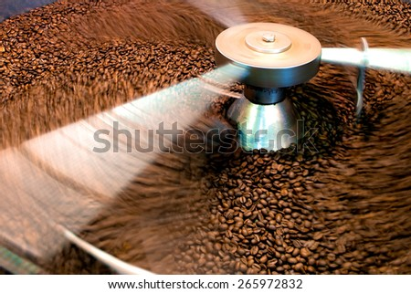 Coffee beans during the roasting process, moving paddle of the screening hopper cooling the coffee beans after roasting. Drum type roaster - stock photo