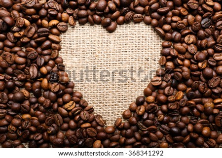 Coffee beans formed heart on burlap background - stock photo