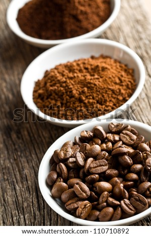 coffee beans, ground coffee and instant coffee in three bowls - stock photo