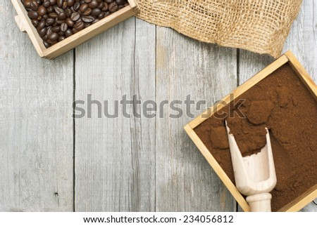 coffee beans, ground coffee with wooden spoon on rusty wood background - stock photo