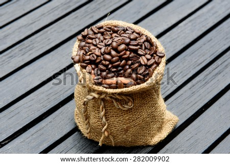 Coffee Beans in a Bag on table - stock photo